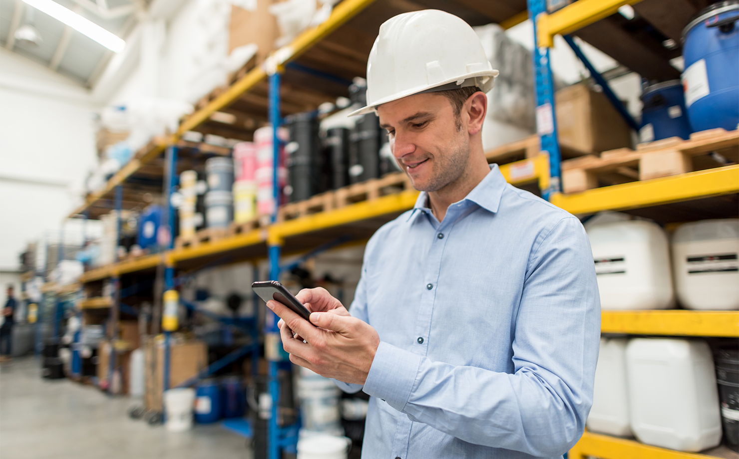 Portrait-of-a-man-working-at-a-warehouse-using-his-cell-phone-856634662_7119x4912