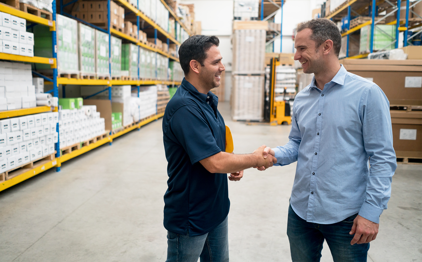 Two-business-men-handshaking-at-a-warehouse-856634734_7952x5304