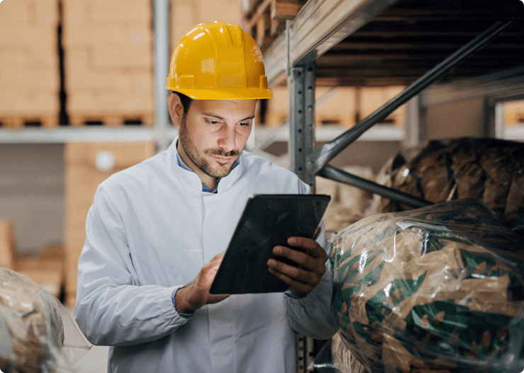 Young-Caucasian-worker-using-tablet-while-standing-in-warehouse.-On-head-helmet.-1061870848_7360x4912